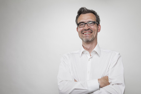 open collar: smiling manager with grayed hair wearing a white shirt with open unbuttoned collar stands next to a white wall Stock Photo