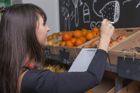 sales assistant: trainee sales assistant counts fruits and vegetables in wooden boxes of a grocery