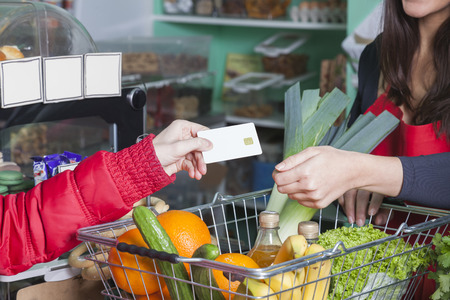 customer hands over a customer card in a greengrocer shop