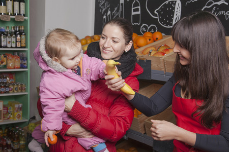 shop assistant: Mother hold her toddler girl in her arms while taking a banana from a shop assistant in the grengrocer