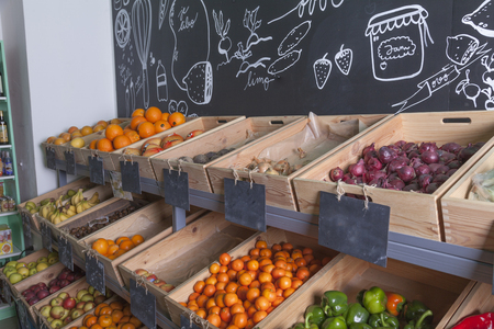 grocer: Fruits and vegetables presented  in a green grocer store in wooden crates