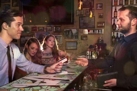bartenders: Man accompanied by two ladies paid the bill at the counter with a credit card