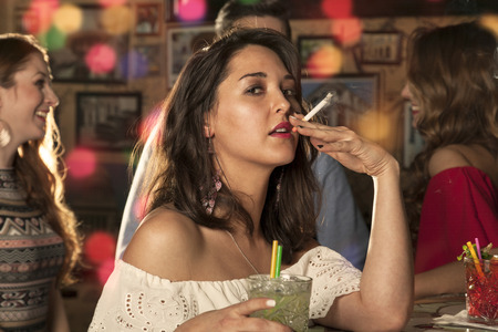 halitosis: Woman looks at you while taking a pull on her cigarette and holding a glass with mojito in her hand. her friends are dancing and chatting in the background Stock Photo