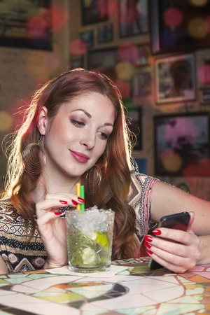 gigolo: Woman reading a message on her mobile phone and drinking a mojito long drink while sitting at the counter of a club
