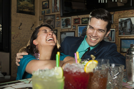 Blind Date: Woman laughs heartily at a joke, to her charming friend who has made while they sit in a cocktail bar and order some drinks