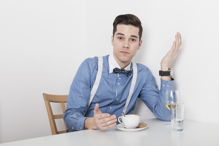 Manager makes a reproachful gesture while a cup of coffee and a glass of wine sitting