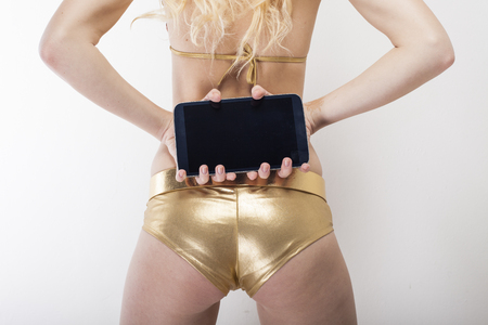 dominant woman: Blond woman captured from behind holding black tablet pc in her hands showing buttocks in golden hot pants