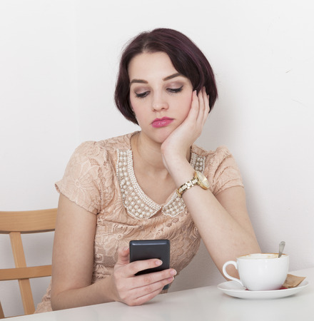 receives: woman receives a message due to canceled date with her in a cafeteria Stock Photo