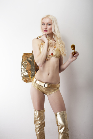 hot pants: longhair blonde in golden bikini and tigh high heel boots and shopping bag