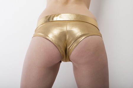 dominant woman: Woman shows sexy buttocks in golden hot pants capture from behind