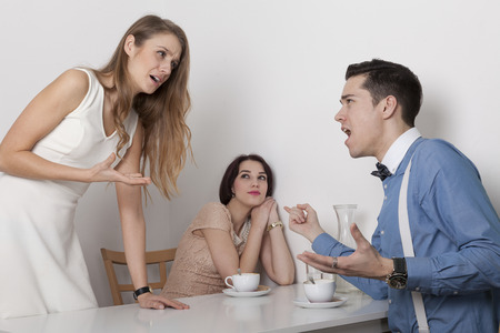 deceive: Firghtened woman looks at screaming couple in cafeteria