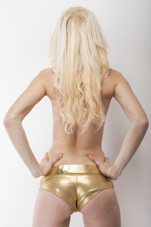 dominant woman: Sexy blonde shows her sexy buttocks in golden hot pants capture from behind