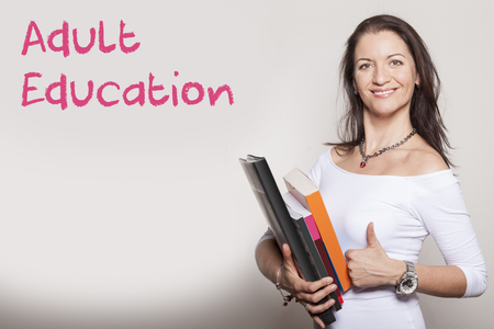 adult student: Female adult student with books holds up thumb Stock Photo