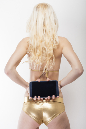 dominant woman: Longhair blonde captured from behind holding black tablet pc in her hands showing buttocks in golden hot pants Stock Photo