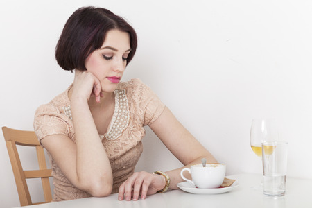 Blind Date: Impatient woman looks at her watch sitting in cafeteria having coffee and wine Stock Photo