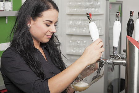 nonalcoholic beer: Hostess taps a fresh draft beer at the bar of her pub
