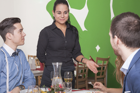 unsatisfied: good mooded waitress makes a suggestion to unsatisfied guests in a restaurant