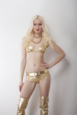 gogo girl: sexy Blondine im Bikini und Hot Pants againt weißen Hintergrund aufwirft
