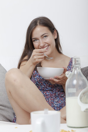 Smiling student sitting cross-legged on the sofa at breakfast