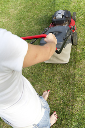 laquered: Woman with laquered feet nails barefoot on the lawn with a lawnmower