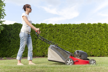 mows: Hobby gardener mows her lawn with a red motor driven lawnmower