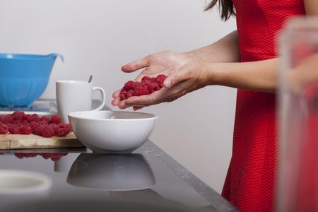 raspberry dress: Woman hands filling fresh raspberries in a dessert bowl