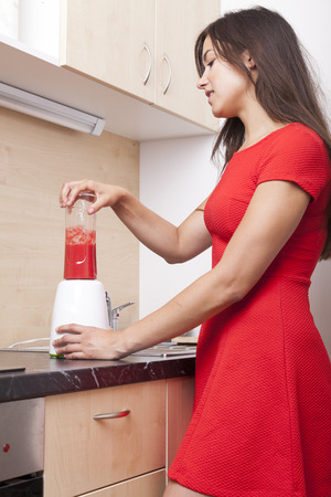raspberry dress: Woman wearing a red mini dress standing is the kitchen preparing herself a smoothie fruit drink