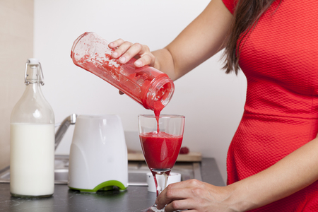 raspberry dress: Woman fills a glass with a red raspberry smoothie