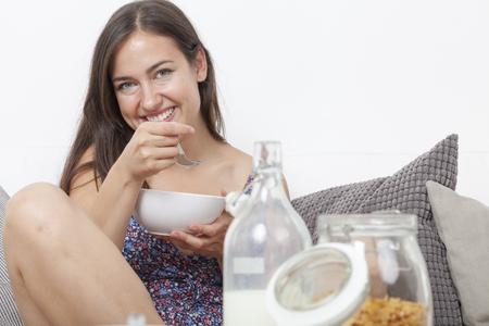 crosslegged: Smiling student sitting cross-legged on the sofa at breakfast