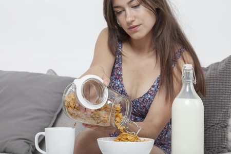 cornflakes: Sexy female student at breakfast of fresh cornflakes with milk Stock Photo