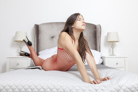 boudoir: Woman in red mesh catsuit enjoys a special feeling Stock Photo