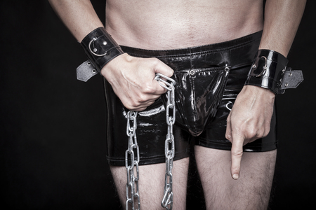 tied down: man in shiny fetish pvc pants makes strong dominant gesture