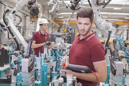 dos ingenieros comprobar el funcionamiento durante la puesta en una línea de producción en el taller de soldadura Foto de archivo