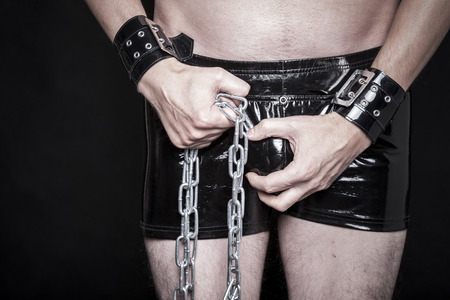 man in shiny fetish pvc pants makes strong dominant gesture