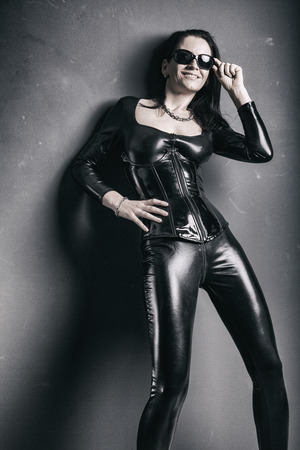 dominant woman in shiny pvc catsuit with sunglasses smiling
