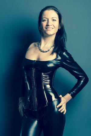 woman in shiny rubber corset and catsuit strokes her hips