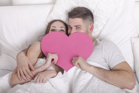 love proof: couple holds pink heart symbol covering their faces while lying in bed Stock Photo