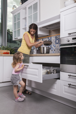 female toddler child opens drawer in the kitchen to help her mother cooking