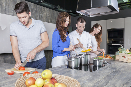 friends in the kitchen prepare a meal together Stock Photo