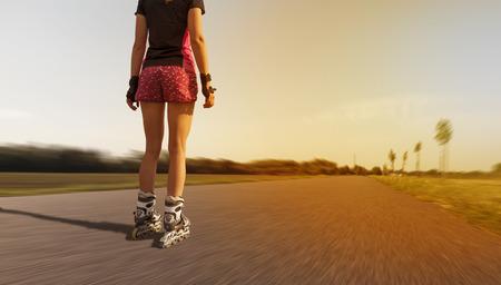 tienermeisje met inline-schaatsen met hoge snelheid op de asfaltweg Stockfoto