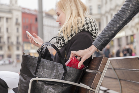 Zakkenroller steelt het portemonnee van een vrouw uit haar handtas in het avondconcept Stockfoto