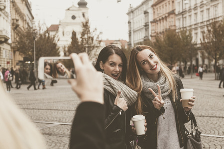 passer-by takes a photo of a silly female couple posing and making tags Banco de Imagens