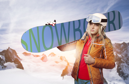 Portrait of a snowboarder with snowboard standing in front of wintry mountain panorama looking into the camera