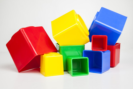 a group of colurful toy blocks unsorted wild lying against white background Foto de archivo