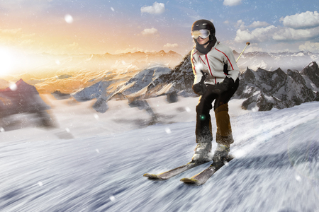 skier rides downhill with high speed besides the sunset