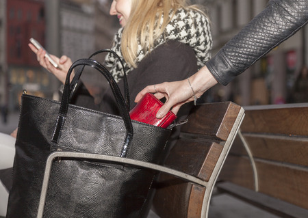 Pickpocket steals a womans purse from her handbag in the evening
