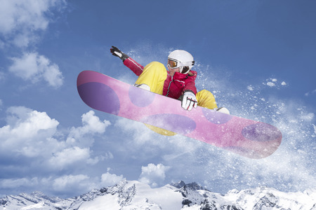 Snowboarder in red jacket and yellow trousers jumps on her snowboard through the air in front of a mountain panorama and winter landscape