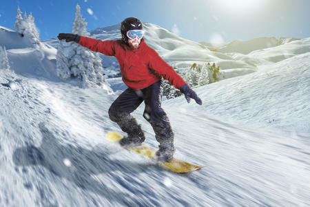Snowboarder slides high speed downhill in a beautiful snowy mountain landscape with powder snow and white hills