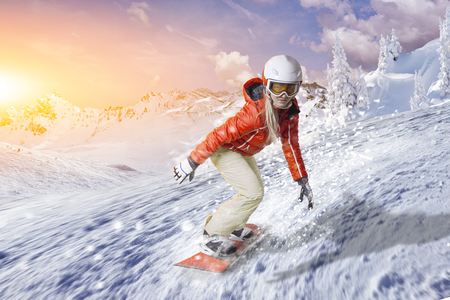Snowboarder in orange hoodie and white pants glides on an orange snowboard over the fresh snow in a wintry mountain landscape Stock Photo