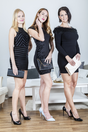 Three women in fashionable party dresses